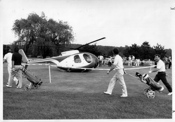 Helicopters - Emergency Landing<br /> Rainbow Helicopter sitting on the fairway of the 10th hole where it had made an emergency landing, as golfers pass by. The landing was on the Whirlpool Public Golf Course.<br /> Photo - By Ron Schifferle - 5/31/1989.