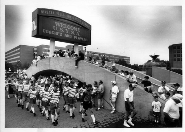 Sports - Soccer<br /> Soccer players march by the Convention Center sign which welcomes them. <br /> Photo - By Elisa Olderman - 6/29/1990.