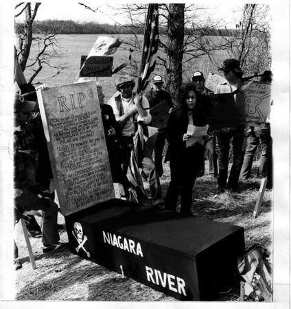 "Citizen - Against pollution.<br /> Niagara Falls, N.Y. April 1, 1980 - Daniell Degolier, standing center, president of Citizens Against Pollution, reads a paper at ""death watch"" at Peggy's Eddy on the Niagara River in Lewiston.<br /> Photo - By John Kudla - 4/1/1981."