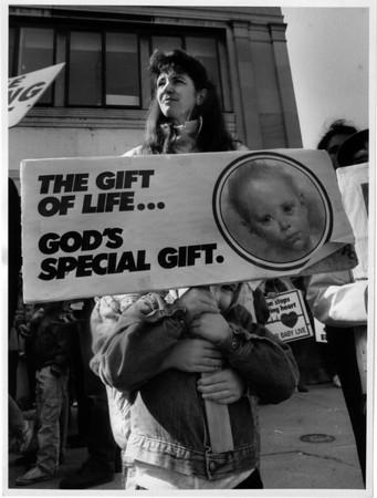 Organizations - Abortion <br /> A small boy peeks from under a sign he and his sister were holding. The mother refused to give their names. Pro-Lifers on High Street across from the General Medical Tower.<br /> Photo - By James Neiss - 4/23/1992.