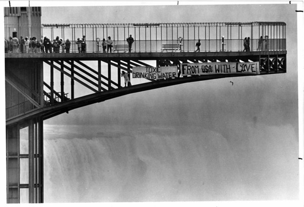 Toxic waste - Greenpeace Protest<br /> Laurie Roberts a Greenpeace member from Chicago Hoist a sign on the Prospect Point observation tower above the American Falls. They were protesting the discharge of Toxic chemicals into the Niagara River from the Niagara Falls Wastewater Treatment Plant.<br /> Photo - By Ron Schifferle - 6/13/1985.