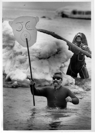 Parks - Gummer Ordway, of Thatcherville, N.Y., carries a big polar bear sign as he wades into the chilly waters of Olcott Beach. A special teams scuba diver, in background, is ready in case of an accident.<br /> Photo - By Elisa Olderman - 3/1/1992.