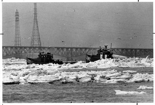 Niagara River - Ice Breakers<br /> New York Power Authority Ice Breaker and the Ontario Hydro Ice Breaker Niagara Queen clears ice in the Niagara River. The picture was taken from Goat Island with a 600mm lens, with the North Grand Island Bridge in the background.<br /> Photo - By Ron Schifferle - 3/5/1985.
