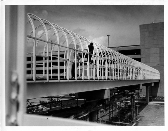 Buildings - Niagara Falls <br /> Rainbow Center<br /> Tightening the bolts as archway is now ready to be enclosed in glass.<br /> Photo - By Andrew J. Susty - 6/14/1982.