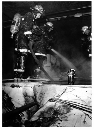 Industries <br /> Firefighters on top of paper rolls put out fire. In building 10 of old Nitec. was storing paper rolls.<br /> Photo - By Tim Johnson - 4/12/1986.