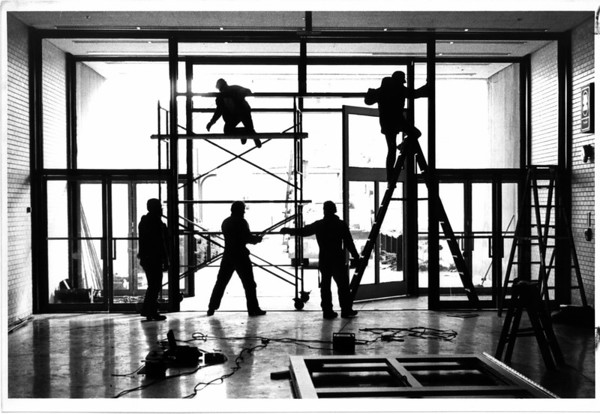 Convention Center<br /> Under construction<br /> Workman from American Glass and Mirror Company of Niagara Falls are installing larger doors at the South end of the Niagara Falls Convention and Civic Center to allow large boats to use the front lobbyduring the up coming boat show. The $14,000.00 job was paid for by the boat show people.<br /> Photo - By Ron Schifferle - 1/23/1986.