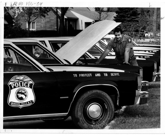 Police - New fleet of police cars to go in service. Bob monroe, Communications Technician looks over the new cars he will equip with roof lights, police radios, and other electrical equipment.<br /> Photo - By Ron Schifferle 11/1/1983.