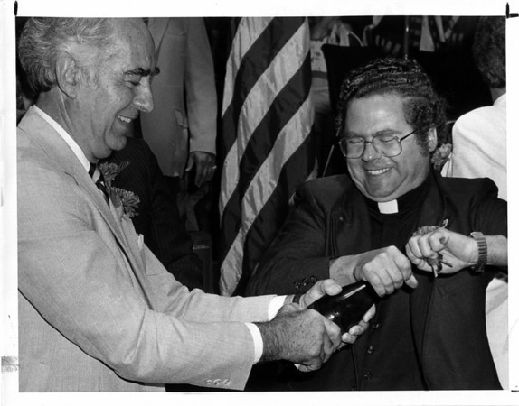 Buildings - Niagar Falls<br /> Rainbow Center<br /> The Mayor's champagne bottle wouldn't open - little assistance from the clergy with his car keys.<br /> Michael O'Laughlin - Mayor, and Rev. Louis M. Lenssen - Niagar Falls Tourist Advisory Board - from Our Lady of Fatima Shrine.<br /> Photo - By Andrew J. Susty - 7/2/1982.