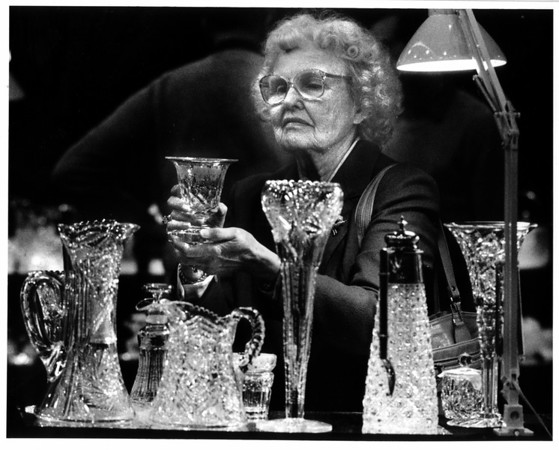 Convention Center - Bookings<br /> Antique Show<br /> Evelyn McCarthy of Laughlin Drive in Niagara Falls Looks at a piece of cut glass, ( an era from 1880 - 1920) at the jamison Antiques booth at the Convention Center.<br /> Photo - By James Neiss - 11/4/1988.