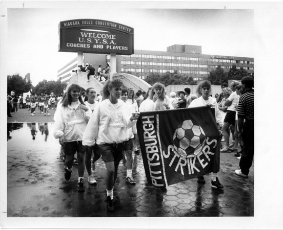 Convention Center Plaza<br /> Lady soccer players , from Pittsburgh, Penn. carry their banner and parade past thousands of people at E. Dent Lackey Plaza.<br /> Photo - By Elisa Olderman - 6/29/1990.