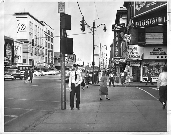 """Urban Renewal - Traffic Control Box<br /> Control Box is out of the Officer's reach.  Officer R. Wolfe standing under the box is 5' 11"""" tall and can not reach the control box.<br /> Photo - By William Corcoran - 9/29/1953."""