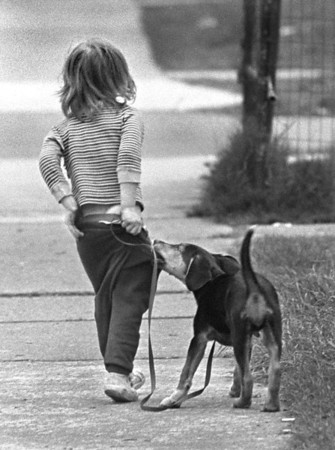 5/8/1989 - Four-year-old Eric Shimmel has a tough time keeping his drawers from droppin monday outside his home at 1312 Walnut Ave., thanks to the antics of his 3-month old puppy, Whiskey.