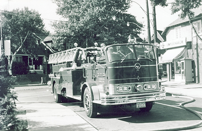 Toronto's 1962 100' Mack aerial, one of only two purchased by the TFD. Shown at a fire at Gerrard St. E and Bowmore Rd. in 1965. The building in the background is now McCarthy's Irish Pub. The company was disbanded in 1994. <br /> <br /> Photo property of Neil McCarten.<br /> <br /> Courtesy of Jon Lasiuk.