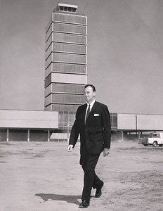 Francis T. Fox, general manager, Department of Airports, takes inspection tour of the construction area of the new L. A. International Airport terminal. In the background is the newly completed Control Tower-Administration Building.