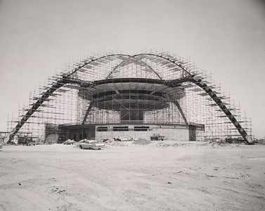 View of the Theme Building under constuction, with scaffolding erected for plastering arches and undersides of the restaurant and observation deck.