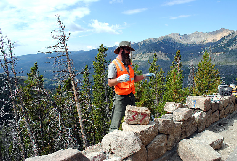 Louis Browning demonstrates how he and fellow mason Kaeli Roman, not pictured, remove each rock and number it as they repair historic rock walls in Rocky Mountain National Park. They store the rocks in order on palates, then after rebuilding the base, replace each rock as it was originally placed.  (Photo by Pamela Johnson/Loveland Reporter-Herald)