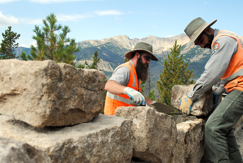 Kaeli Roman, right, and Louis Browning, masons who work for Rocky Mountain National Park, replace one rock at a time on a historic wall the Civilian Conservation Corps built by hand in about 70 years ago. The team repairs one stretch of rock each summer, this year focusing on 150 feet on Trail Ridge Road.  (Photo by Pamela Johnson/Loveland Reporter-Herald)