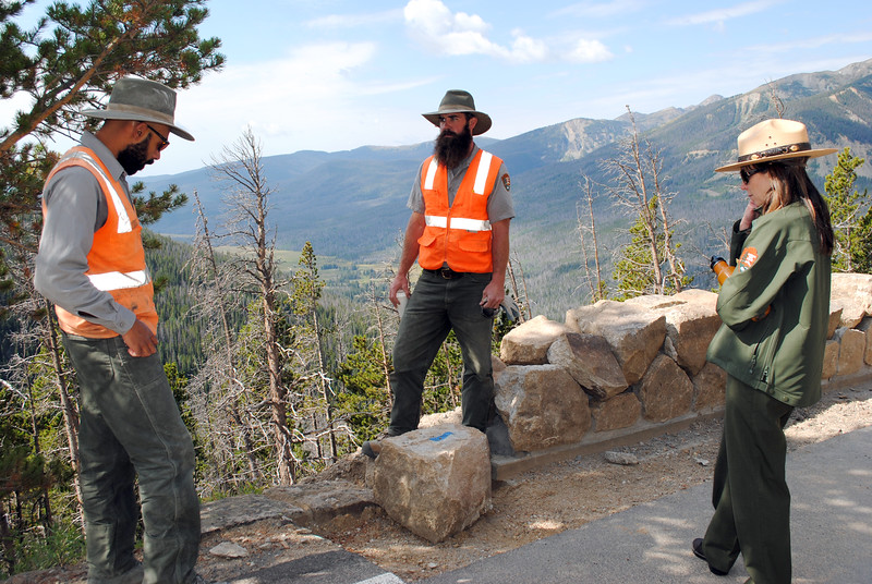 The stretch of rock wall in front of Louis Browning, center, shows how it had sunk almost fully into the ground before Browning and Kaeli Roman, at left, excavated and rebuilt the stone work in Rocky Mountain National Park. The stretch behind Browning shows the height of the wall as restoration nears completion. Park spokeswoman Kyle Patterson, at right, listens as the team explains its process.<br /> (Photo by Pamela Johnson/Loveland Reporter-Herald)