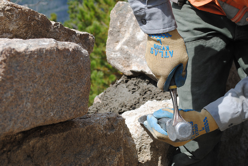 Craftsman about 70 years ago hand cut each rock to fit together like a puzzle for walls places throughout Rocky Mountain National Park. Recently, craftsman Kaeli Roman chiseled a tiny amount off this rock to replace it in its original location.   (Photo by Pamela Johnson/Loveland Reporter-Herald)