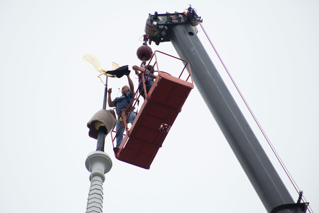 """. Contractor Bob Levesque Jr. removes the wrappings on a restored rooster-shaped weather vane, nicknamed \""""Buddy,\"""" on top of the Old Groton Meetinghouse on Saturday. Lowell Sun/Chris Lisinski"""