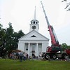 Onlookers watch a crane prepare to lift a restored weather vane to the top of the Old Groton Meetinghouse on Saturday. Lowell Sun/Chris Lisinski