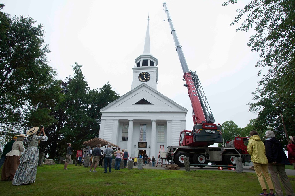 . Onlookers watch a crane prepare to lift a restored weather vane to the top of the Old Groton Meetinghouse on Saturday. Lowell Sun/Chris Lisinski