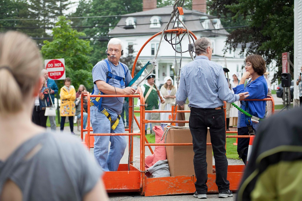 . Contractor Bob Levesque Jr. (left) and architect Lynne Spencer (right) prepare to ride a crane to the top of the Old Groton Meetinghouse on Saturday. Lowell Sun/Chris Lisinski