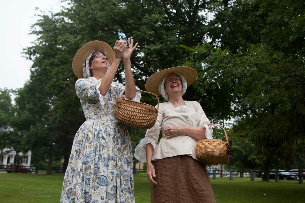 """. Christine Griffin (left) of Holden and Ginny Babin of Groton, both dressed as what Babin called \""""1775 eye candy,\"""" observe the re-installation of a historic weather vane at the Old Groton Meetinghouse on Saturday. Lowell Sun/Chris Lisinski"""