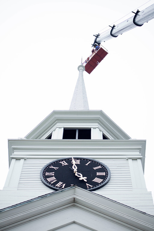 . Contractors riding a crane re-attach a restored weather vane to the top of the Old Groton Meetinghouse on Saturday. Lowell Sun/Chris Lisinski