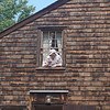 A woman dressed in colonial-era attire waved from the window at the Job Lane House, which is located in what used to be Billerica. Photo by Beth Douglas
