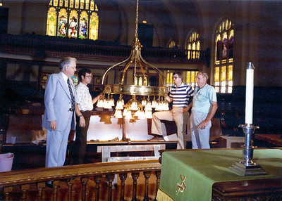 Church member, Harold Rose, far right, admires Sanctuary light he restored while Rev. Robert Dickerson, far left, and Alan Gantzhorn, 2nd from left, look on.