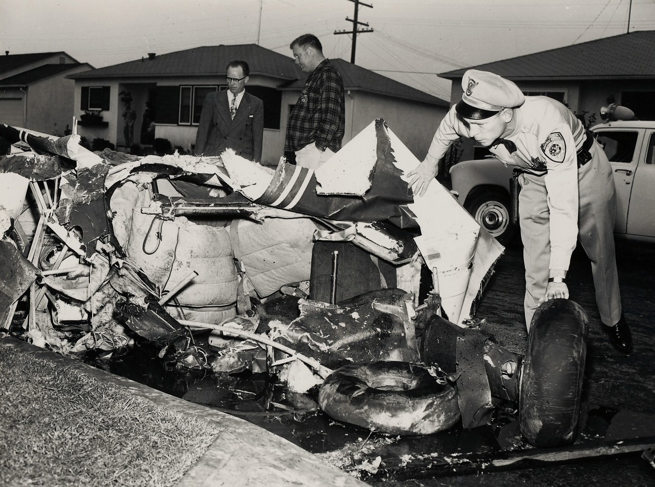 """California Highway Patrolman Mike O'Leary inspects the crushed cockpit and cabin of the Stinson. <br /> <br /> Patrolman O'Leary was directing traffic a block from the scene on El Segundo Boulevard. <br /> <br /> Here is Patrolman O'Leary's account: """"I looked up when the motor roared, then I saw him sort of roll over, then the ship dived and seemed to explode""""."""