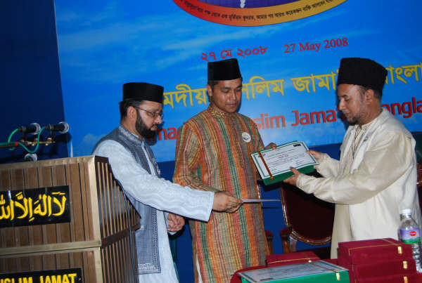 Essay competition 1st Prize winner among Khuddam Ehsanul Habib Joy receiving Prize from National Ameer sb.