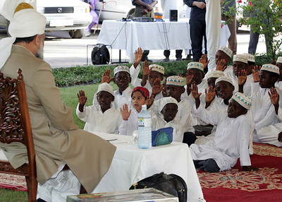 Children raise hands while singing