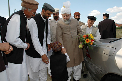 Huzur meets with a waqf-e-Nau child after accepting flowers from him