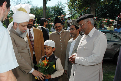 Huzur was welcomed with flowers presented by a child