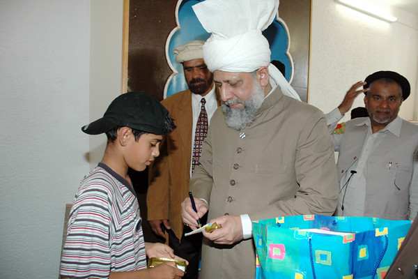 Huzur gives a pen to children