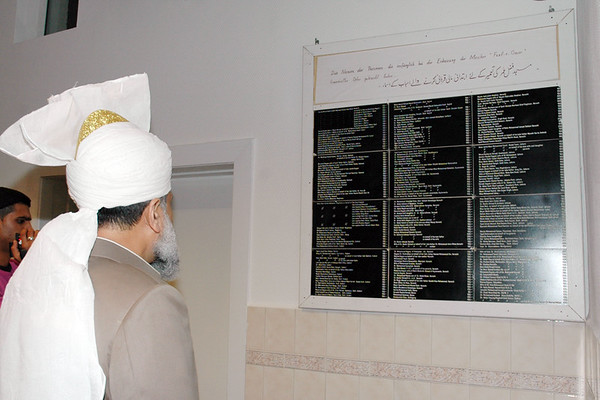 Huzur reading the board with names of people who donated money for this mosque