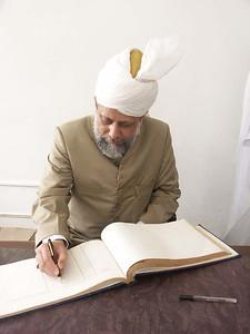 Hazrat Khalifatul Masih V signing the visitors book at the TI Ahmadiyya College