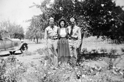 Young men in military uniforms posing with woman in an orchard, c. 1945