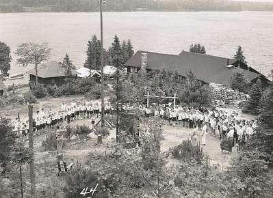 The entire camp gathered at flagpole, with a newly planted Stalker Park in front of the Dining Hall. Daily grace at mealtimes, flag ceremonies, and bugle calls were all part of the daily routines.