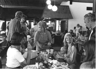 Joan Klaussen, Brett Jones (seated), Ramona Moon (seated), David Perlman (standing, right). Community meal. 1976.