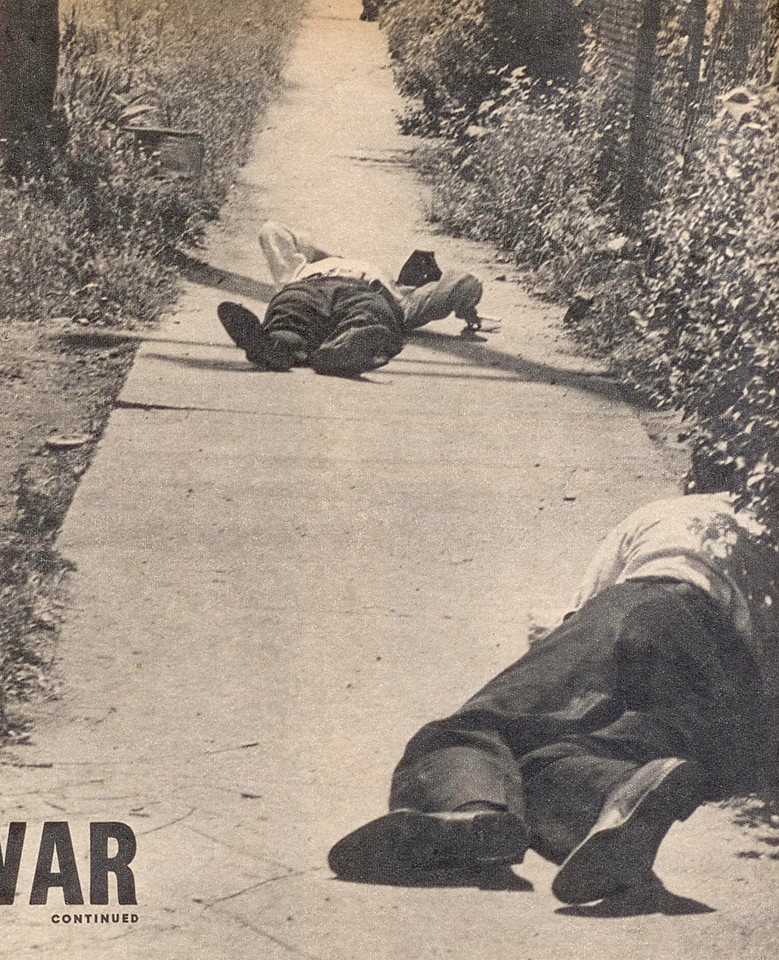 Officer crawls toward wounded Dora Ward, just prior to being shot.