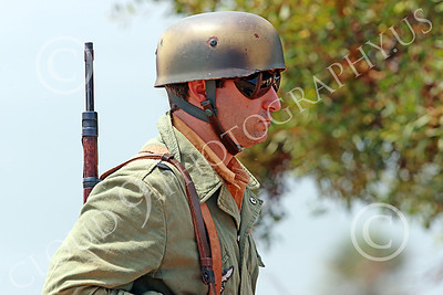 HR-WWIIGAS 00008 A convincing re-enactment of a WWII German Army soldier with sunglasses, helmet, and rifle, historical re-enactor picture by Peter J Mancus