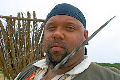 HR-PIR 00006 A burly Black male historical reenactor pirate looks across his sword's blade, by Peter J Mancus