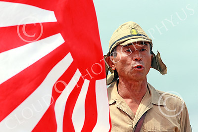 HR-WWIIIJS 00002 A World War II Imperial Japanese Army soldier sounds off while holding the Japanese rising sun flag, historical re-enactor picture by Peter J Mancus