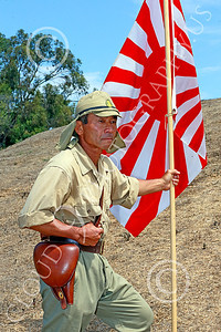 HR-WWIIIJS 00013 A World War II Imperial Japanese Army soldier with pistol holster and flag stands on the side of a hill, historical re-enactor picture by Peter J Mancus