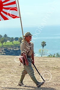 HR-WWIIIJS 00027 A World War II Imperial Japanese Army soldier with sword carries the Japanese rising sun flag before the Pacific Ocean, historical re-enactor picture by Peter J Mancus