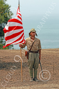 HR-WWIIIJS 00005 A conquering World War II Imperial Japanese Army soldier stands poudly with his flag and sword near the Pacific Ocean as a back drop, historical re-enactor picture by Peter J Mancus