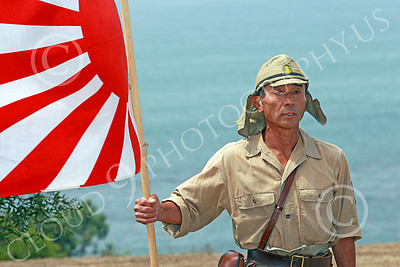 HR-WWIIIJS 00026 A World War II Imperial Japanese Army soldier stand with the Japanese rising sun flag with the Pacific Ocean in the background, historical re-enactor picture by Peter J Mancus